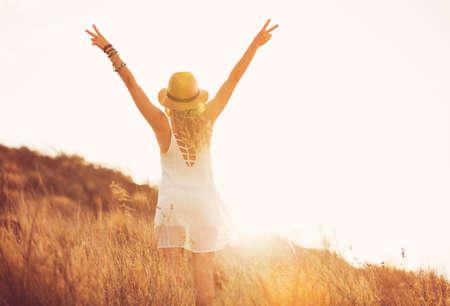 Gelukkig zorgeloze jonge vrouw buitenshuis. Fashion Lifestyle portret. Zachte warme zonnige kleuren.
