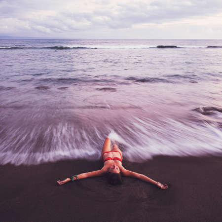 float: Beautiful Woman Relaxing on Tropical Beach at Sunset