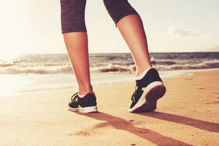 Close up of runners feet at Sunset. Fitness woman, workout wellness lifestyle concept.