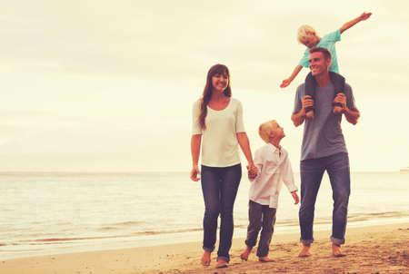 Gelukkige jonge familie op het strand bij zonsondergang