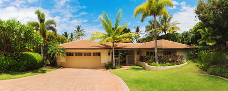 stucco: Tropical Luxury Home, Exterior View with Green Lawn and Driveway