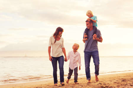 행복 한 젊은 가족 해질녘 해변에서 재미 걷는 데