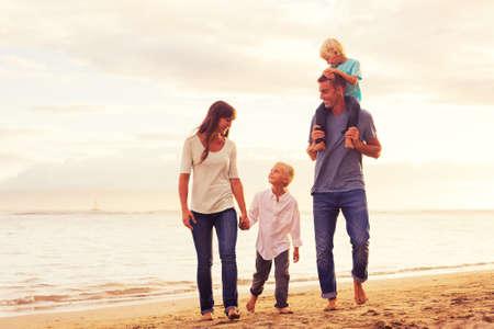 Heureux jeune famille ayant marche amuser sur la plage au coucher du soleil Banque d'images