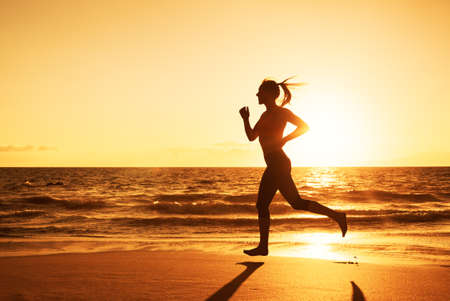 people in action: Woman Running on the Beach at Sunset Stock Photo