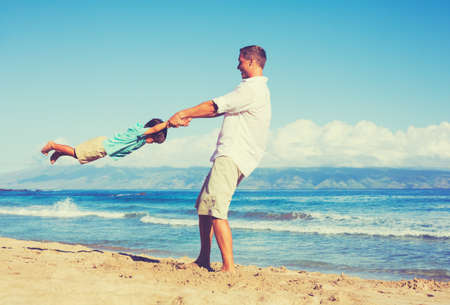 flying man: Happy father and son playing together at the beach. Fun vacation summer lifestyle.