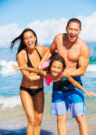 Young Happy Family Playing Having Fun at the Beach Outdoors photo