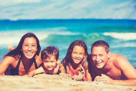 Giovane famiglia felice divertirsi in spiaggia esterna