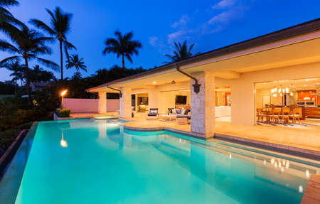 夕暮れ時のプールのある美しい高級ホーム