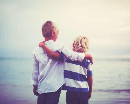 兄弟、夕暮れを抱いて幸せな若い兄弟。友情の同業組合の概念