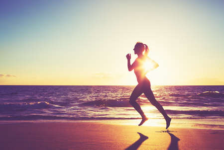 jogging: Woman Running on the Beach at Sunset Stock Photo