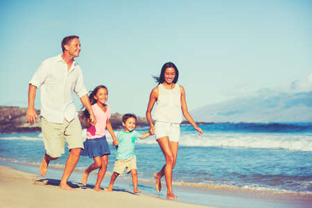 interracial family: Young Happy Family Having Fun on the Beach Outdoors