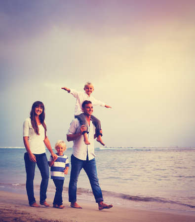 Happy young family on the beach at sunset