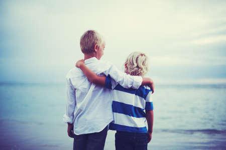 Broers, Gelukkig jonge broers knuffelen bij zonsondergang. Vriendschap broederschap begrip