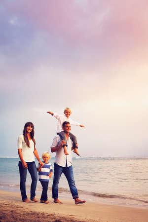 행복 한 젊은 가족 해질녘 해변에서 재미 산책을 갖는