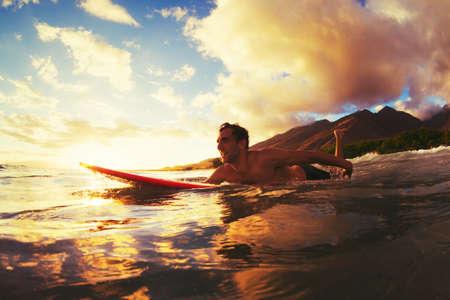 lifestyle: Surfen bij zonsondergang. Outdoor actieve levensstijl. Stockfoto