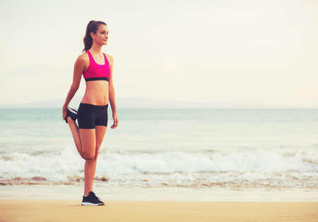 Healthy Active Lifestyle. Young fitness woman stretching on the beach at sunset. Stock Photo