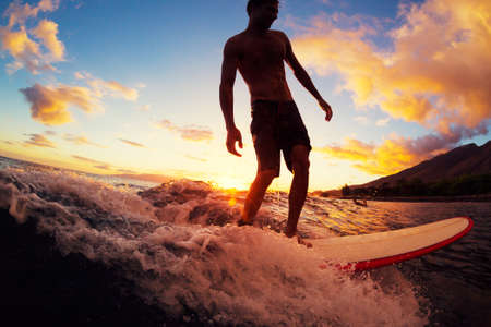 Surfing at Sunset. Young Man Riding Wave at Sunset. Outdoor Active Lifestyle. Stock Photo