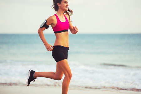 being: Healthy Active Lifestyle. Young sports fitness woman running on the beach at sunset.