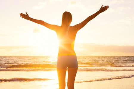Bonne femme de remise en forme réussie levant les bras vers le ciel au coucher du soleil. Succès, célébrant les objectifs et les réalisations. Vie saine et active.