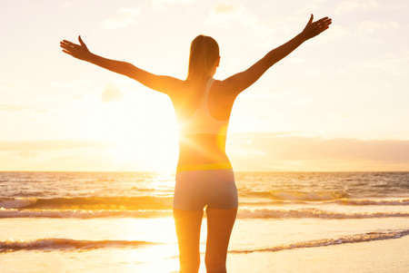 Happy successful fitness woman raising arms to the sky at sunset. Success, celebrating goals and achievement. Healthy Active Lifestyle. Stock Photo