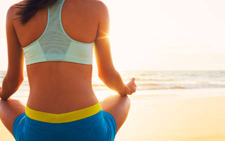 active lifestyle: Happy young woman practicing yoga on the beach at sunset. Healthy active lifestyle concept.