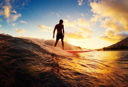 Surfa på solnedgången. Young Man Riding Wave på solnedgången. Utomhus aktiv livsstil.