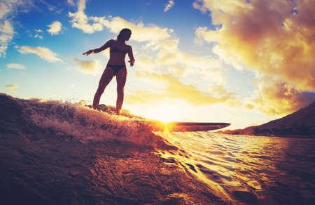 日没でサーフィン。夕暮れの波に乗って美しい若い女性。屋外のアクティブなライフ スタイル。