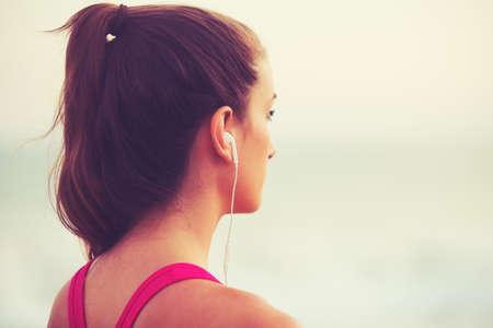escucha activa: Estilo de Vida Activo Deportes con la tecnolog�a moderna. Aptitud de la mujer joven que escucha la m�sica que se resuelve.