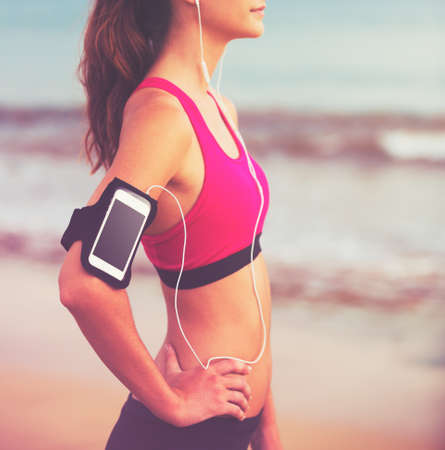 health technology: Active Healthy Sports Lifestyle with Modern Technology. Young attractive fitness woman with smart phone ready for workout. Stock Photo