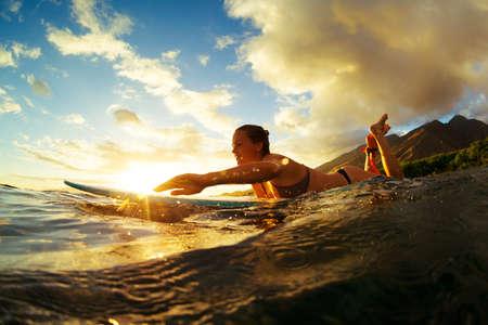 cielo y mar: El practicar surf en la puesta del sol. Estilo de vida activo al aire libre.