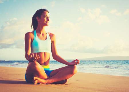 Gelukkige jonge vrouw het beoefenen van yoga op het strand bij zonsondergang. Gezonde actieve levensstijl concept. Stockfoto