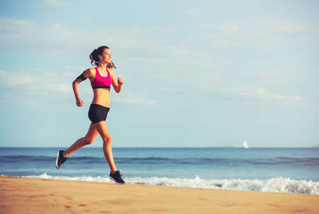 sunshine: Healthy Active Lifestyle. Young sports fitness woman running on the beach at sunset.