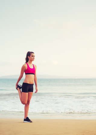active lifestyle: Healthy Active Lifestyle. Young fitness woman stretching and preparing to run on the beach at sunset.