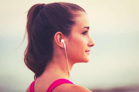 escucha activa: Estilo de Vida Activo Deportes con la tecnolog�a moderna. Aptitud de la mujer joven escuchando m�sica Foto de archivo