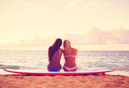 夕暮れ時のビーチでサーファーの女の子。夏のアウトドア。最高のビーチの外の友人たち。