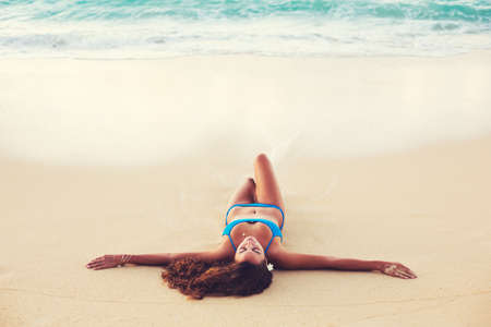 Summer Lifestyle, Beautiful Happy Carefree Young Woman Relaxing on the Beach at Sunset 스톡 콘텐츠