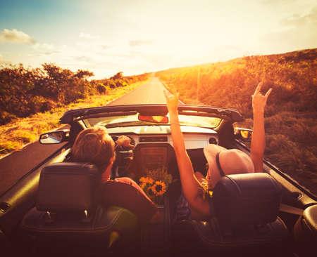若いカップルが夕日で変換可能で田舎道に沿って運転 写真素材