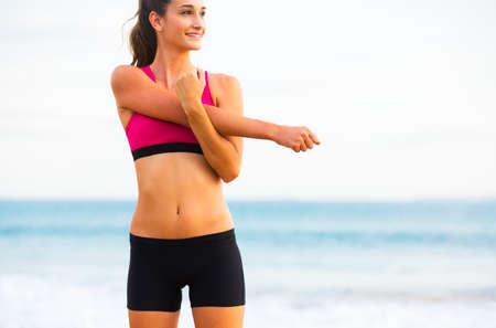 젊은 매력적인 피트니스 여자 해변, 근무 절판에 스트레칭. 건강한 활동적인 야외 생활.