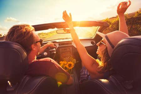 Feliz Pareja Joven Conducción a lo largo la carretera nacional en Convertable en Sunset. Libertad Adevnture Roadtrip!