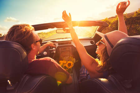 libertad: Feliz Pareja Joven Conducción a lo largo la carretera nacional en Convertable en Sunset. Libertad Adevnture Roadtrip!