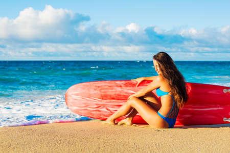 夕暮れ時のビーチの美しいサーファーの女の子。夏のお楽しみアウトドア ライフ スタイル。