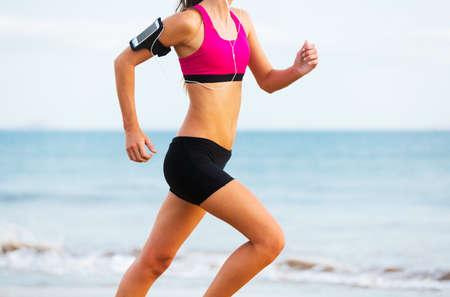 Fitness vrouw loopt door de zee bij zonsondergang