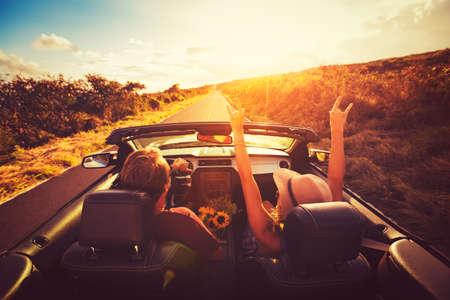 Счастливый молодая пара езды по проселочной дороге в CONVERTABLE на закате. Свобода Adevnture Roadtrip!