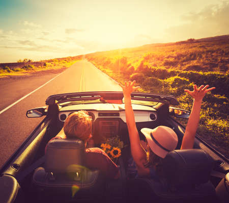 Giovani coppie felici Guidando lungo Strada di campagna in Convertable al tramonto. Libertà Adevnture Roadtrip!