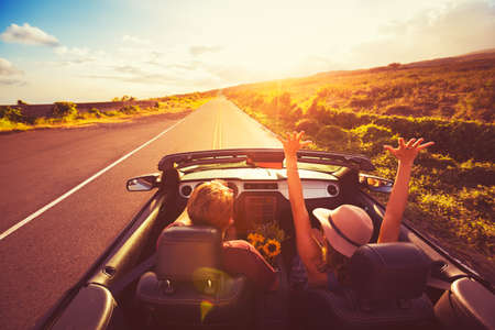 road of love: Happy Young Couple Driving Along Country Road in Convertable at Sunset. Freedom Adevnture Roadtrip!