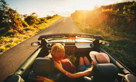 young happy couple: Happy Young Couple Driving Along Country Road in Convertible at Sunset
