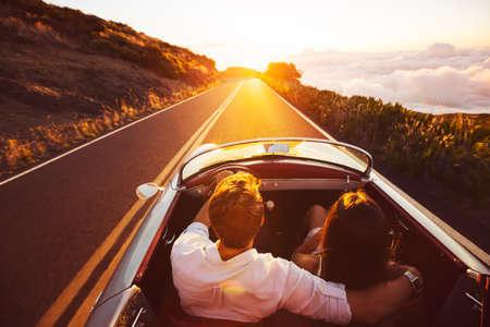 parejas felices: Pareja feliz de conducción en la carretera nacional en el Atardecer en Classic Vintage Sports Car Foto de archivo