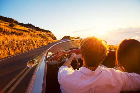 Conduire dans le soleil couchant. Romantique jeune couple Bénéficiant Sunset Drive à vintage classique de voiture de sport Banque d'images - 44182144