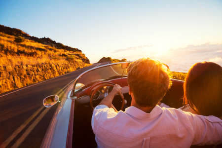 Driving into the Sunset. Romantic Young Couple Enjoying Sunset Drive in Classic Vintage Sports Car Imagens