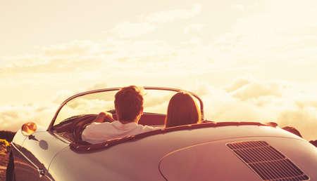 クラシックなビンテージ スポーツカーで夕日を見てロマンチックな若い魅力的なカップル
